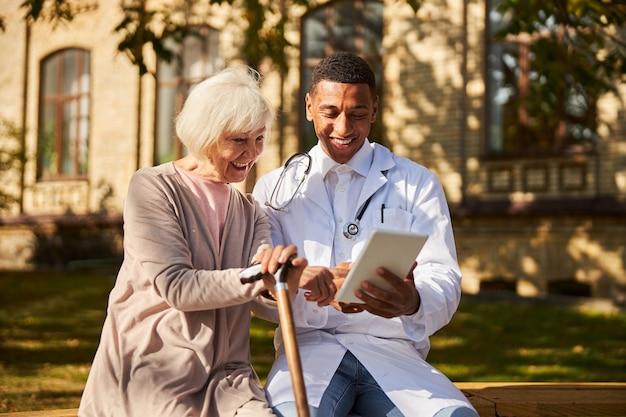 휴대 전화 태블릿의 화면을 두드리는 그의 노인 환자와 흥분된 의사