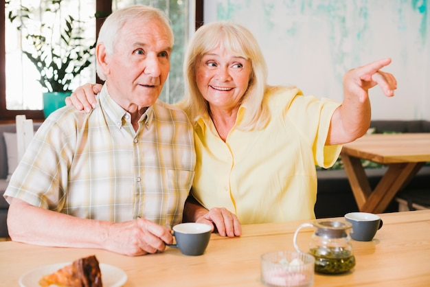 Excited elderly couple looking away