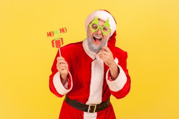 棒にお祝いカード、新年とクリスマスのお祝いを保持しているサンタクロースの衣装を着て灰色のひげを持つ興奮した老人。黄色の背景に分離された屋内スタジオショット。