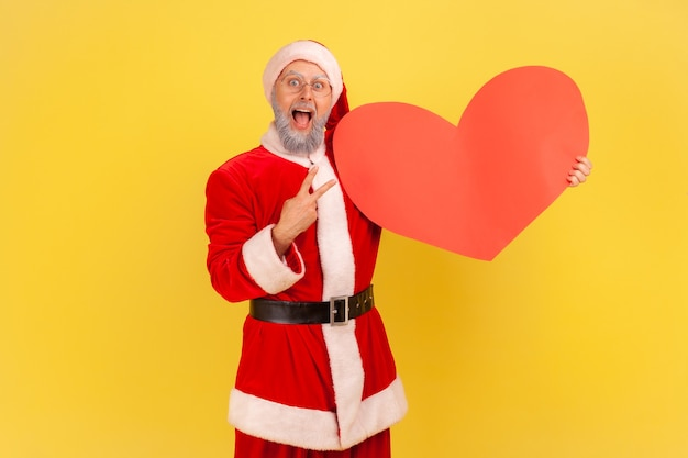 Excited elderly man with gray beard wearing santa claus costume keeps mouth open, showing big red heart and v sign, celebrating holiday. indoor studio shot isolated on yellow background.