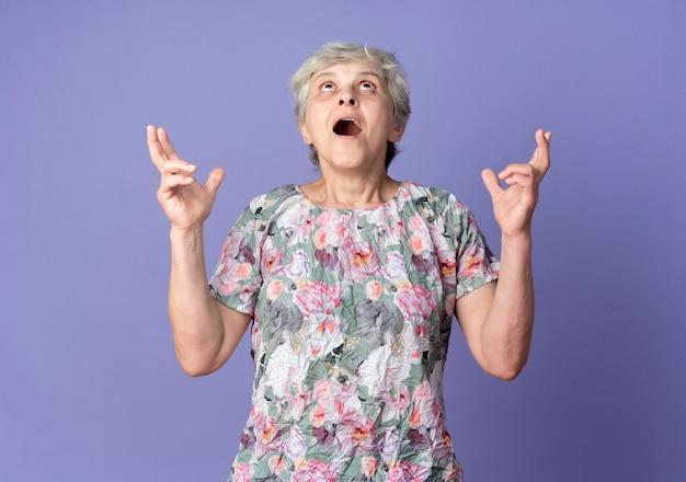 興奮した年配の女性が紫色の壁に孤立して見上げる指を交差させる