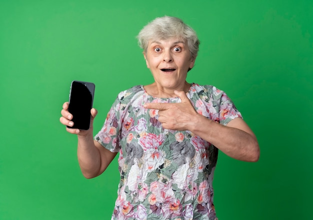 Возбужденная пожилая женщина держит и указывает на телефон, изолированные на зеленой стене
