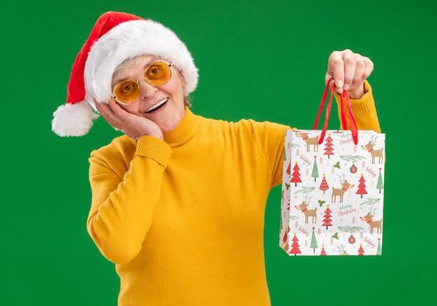 サンタの帽子とサングラスで興奮した年配の女性は、顔に手を置き、コピースペースで緑の背景に分離された紙のギフトバッグを保持します。