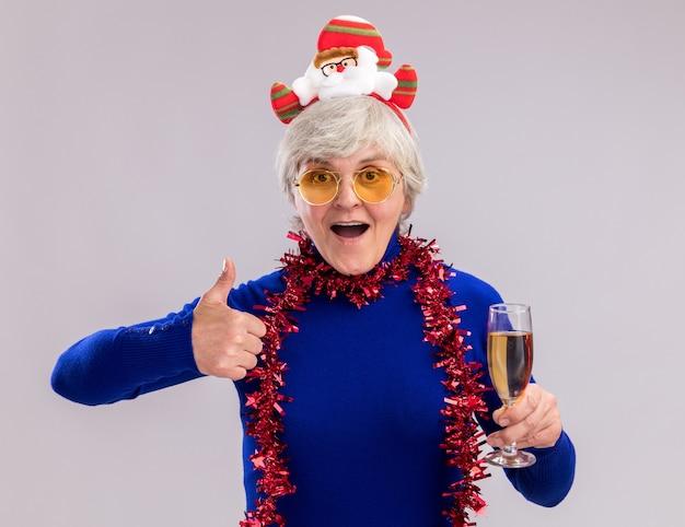 サンタのヘッドバンドと首の周りの花輪とサングラスで興奮した年配の女性は、コピースペースのある白い壁に隔離されたシャンパンと親指のガラスを保持します。