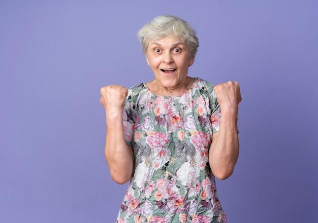興奮した年配の女性は、紫色の壁に孤立した拳を探し続けます