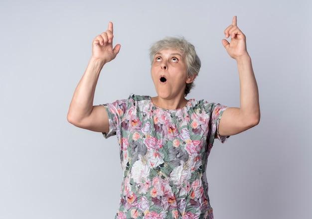 興奮した年配の女性は、白い壁に隔離された両手で見たり、上向きにします