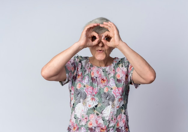 興奮した年配の女性は白い壁に隔離された指を通して見る