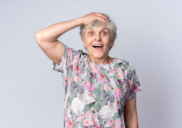 興奮した年配の女性が白い壁に孤立して見上げる頭に手を置く