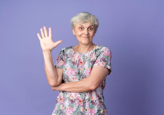 興奮した年配の女性が紫色の壁に隔離された手を上げる