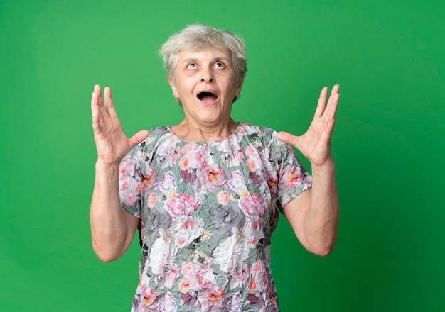 興奮した年配の女性が緑の壁に孤立して見上げる手を上げる