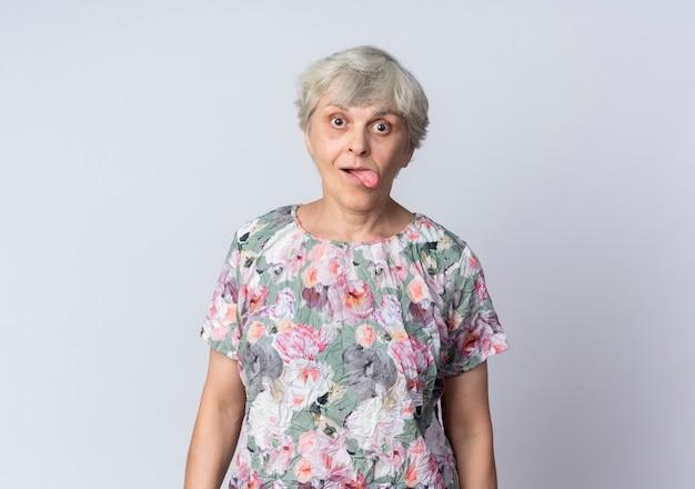 興奮した年配の女性が白い壁に孤立して舌を突き出します