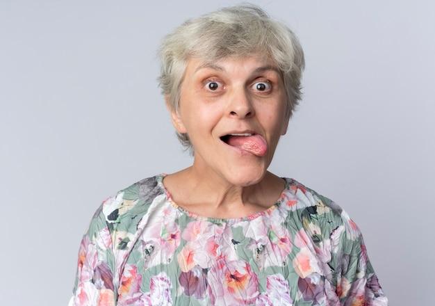 흥분된 노인 여성이 흰 벽에 고립 된 찾고 혀를 튀어 나와