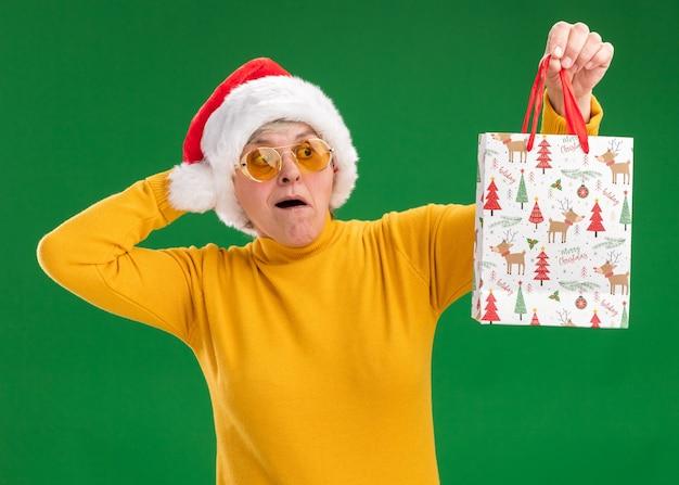Eccitato donna anziana in occhiali da sole con cappello santa mette la mano sulla testa tenendo e guardando il sacchetto regalo di carta