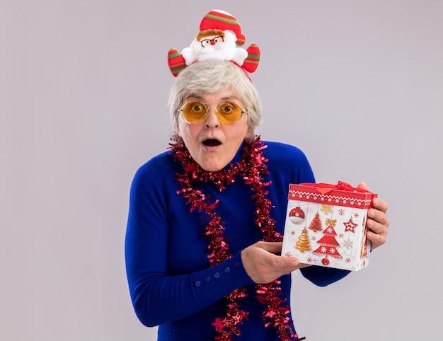 Eccitato donna anziana in occhiali da sole con fascia santa e ghirlanda intorno al collo tiene scatola regalo di natale isolata sul muro bianco con spazio copia