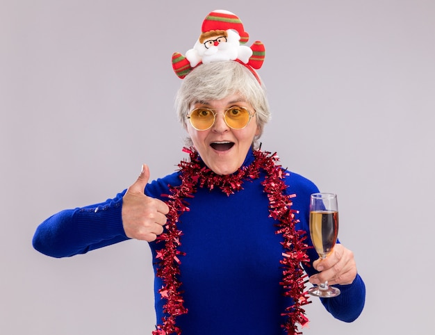 Excited elderly woman in sun glasses with santa headband and garland around neck holds glass of champagne and thumbs up isolated on white wall with copy space