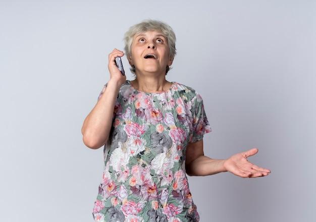 興奮した年配の女性が電話で話し、白い壁に孤立して見上げる