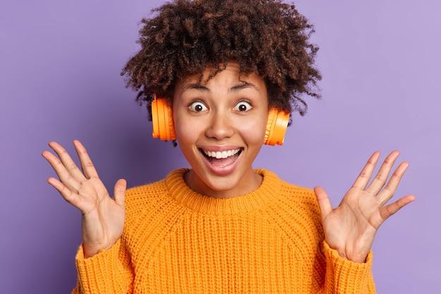 Возбужденная эмоциональная афроамериканка поднимает руки, радостно реагирует на потрясающие новости, слушает любимую музыку в наушниках, носит повседневный оранжевый джемпер