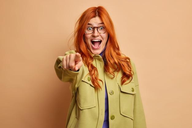 驚きの表情で興奮した感情的な赤毛の女の子は大声で叫び、ポイントはファッショナブルな服を着たあなたを直接選ぶか選択します。