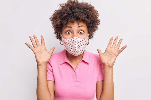 Eccitata donna emotiva fissa gli occhi infastiditi alza i palmi indossa una maschera protettiva usa e getta per prevenire la diffusione del coronavirus rimane in autoisolamento durante la quarantena isolata sul muro bianco