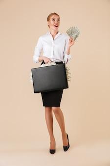 Возбужденная эмоциональная молодая бизнес-леди, держащая чемодан с деньгами.