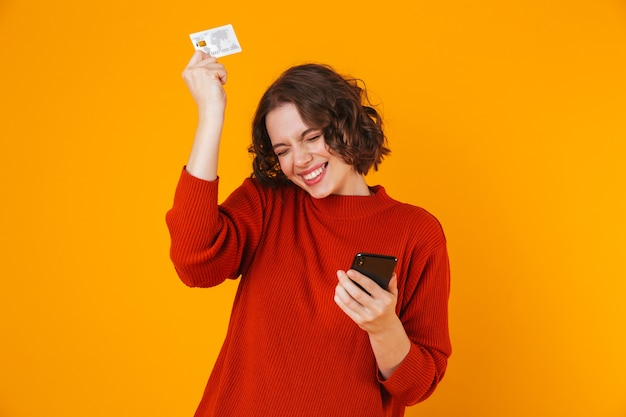 Excited emotional young pretty woman posing isolated on yellow wall using mobile phone holding credit card.