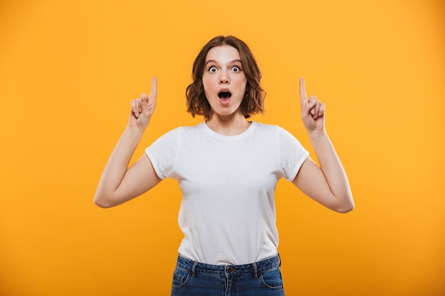 Excited emotional young woman showing copyspace.