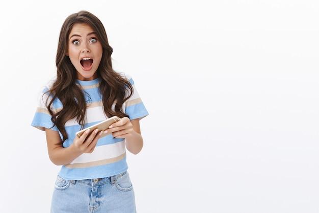 흥분하고 쾌활한 귀여운 소녀는 모바일 게임을 하는 방법을 배우고 스마트폰을 수평으로 잡고 소리를 지르며 놀란 응시 카메라에 매료되어 멋진 아케이드를 플레이합니다