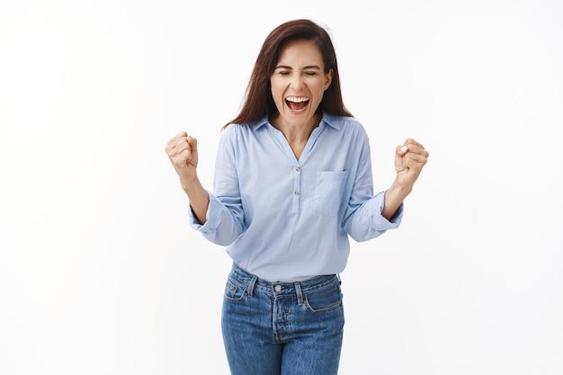 Eccitato incoraggiato, motivato bella donna adulta urla evviva sì, pompa pugno con gioia, celebra la vittoria, trionfando ottimista, chiudi gli occhi urlando felicemente, stai in piedi sul muro bianco