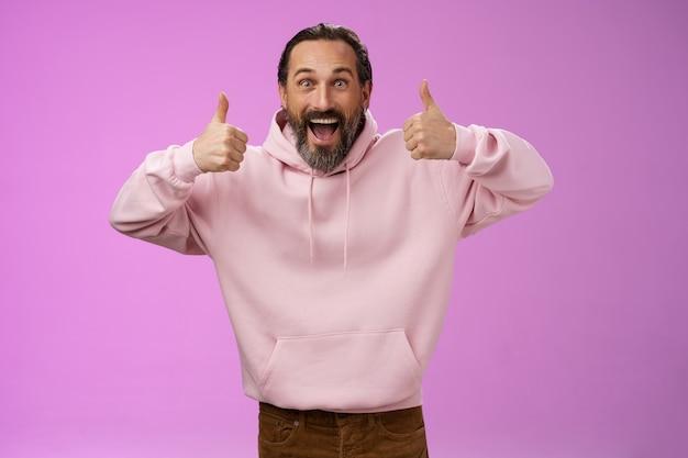 ピンクのパーカーで興奮した活気に満ちた支持的なカリスマ的なヨーロッパの成熟したひげを生やした男は、笑顔で親指を立てて、素晴らしい製品を推奨することを承認し、紫色の背景に立って満足しています。