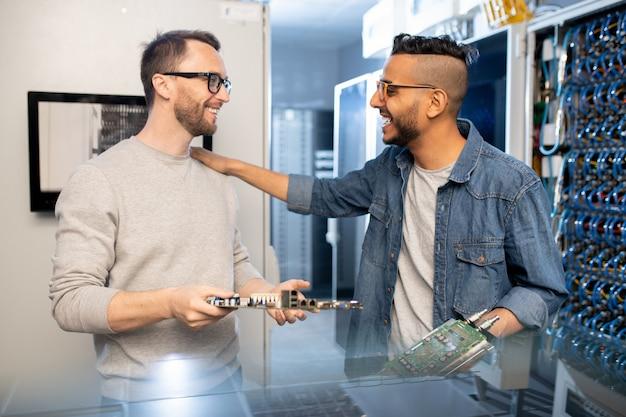 Excited engineers repairing motherboards in server room