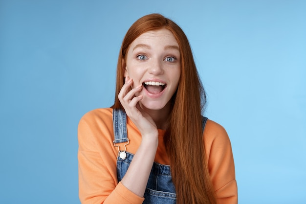 Excited enthusiasitc charismatic redhead female friend look surprised amused touch cheek open mouth thrilled discussing future prom rejoicing standing blue background joyful delighted.