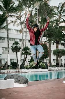 Excited ethnic guy leaping up on poolside