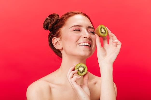 Kiwi europeo emozionante della holding della ragazza. studio shot di donna spensierata con frutti esotici isolati su sfondo rosso.