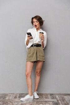 テイクアウトコーヒーを保持し、灰色の壁に隔離されたスマートフォンを使用して興奮したヨーロッパの女性
