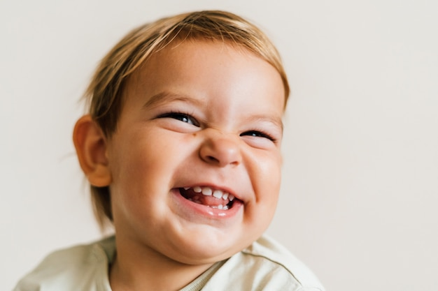 Excited face of a small baby toddler on white background