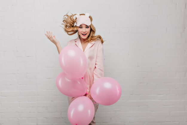 Excited fair-haired girl in pink pajamas holding bunch of helium balloons. indoor portrait of inspired young lady in trendy sleep mask dancing on light wall.