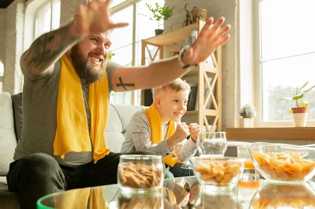 家でサッカー、スポーツの試合を見ている興奮した家族。全国のバスケットボール、サッカー、テニス、サッカー、ホッケーチームのテレビチャンネルを探している父と息子。感情、サポート、応援の概念。