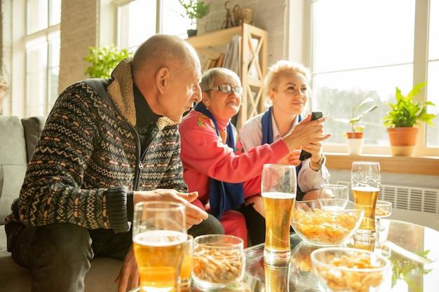 サッカーを見ている興奮した家族、自宅でのスポーツの試合、父と息子