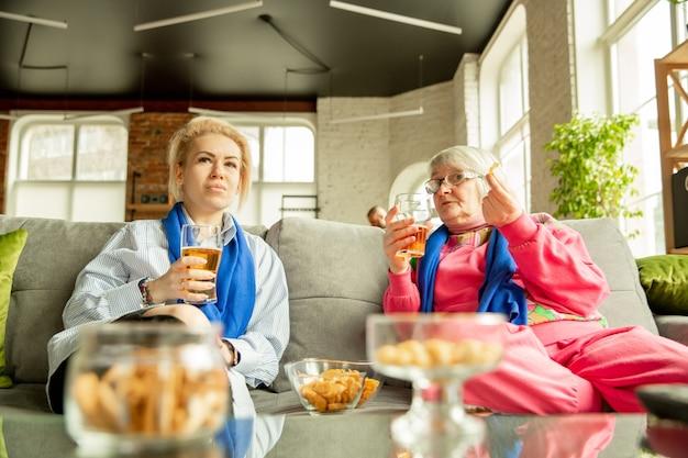 サッカーを見ている興奮した家族、自宅でのスポーツの試合、おばあちゃんと娘