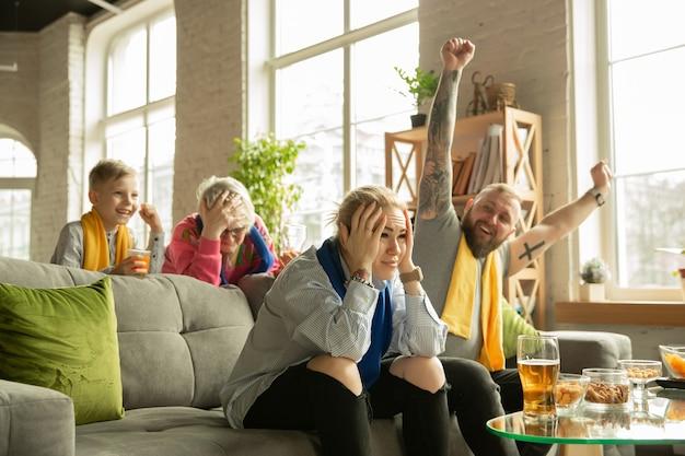 家でサッカー、スポーツの試合を見ている興奮した家族。祖父母、両親、子供がお気に入りの全国バスケットボール、サッカー、テニス、サッカー、ホッケーチームを応援しています。感情の概念、サポート。