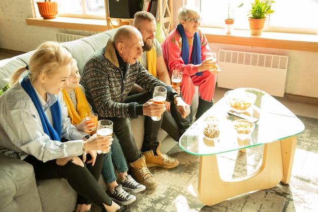 Взволнованная семья смотрит футбол, спортивный матч дома. бабушки и дедушки, родители и дети болеют за любимую сборную по баскетболу, футболу, теннису, футболу, хоккею. понятие эмоций, поддержки.