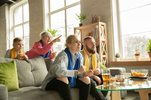 家でサッカー、スポーツの試合を見ている興奮した家族。祖父母、両親、子供がお気に入りの全国バスケットボール、サッカー、テニス、サッカー、ホッケーチームを応援しています。感情の概念、サポート。 Premium写真