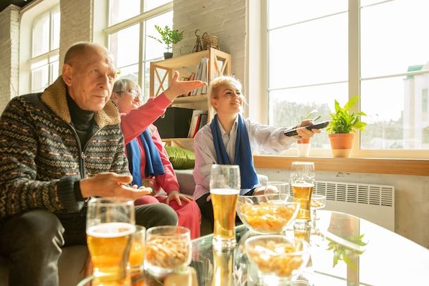 サッカーを見ている興奮した家族、自宅でのスポーツの試合、上面図