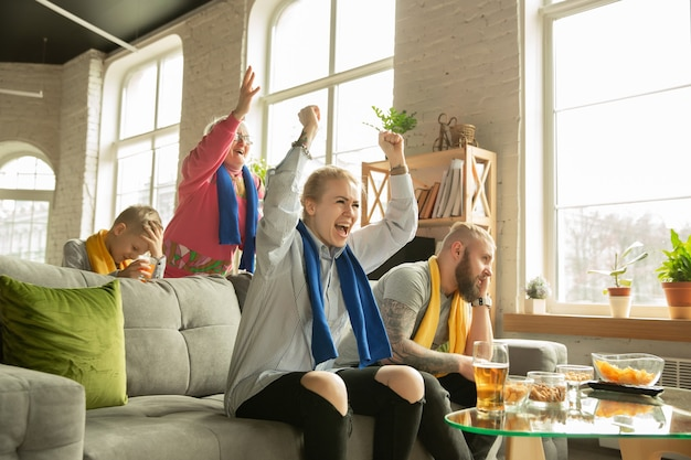 Excited family watching football, sport match at home. grandparents, parents and kid cheering for favourite national basketball, football, tennis, soccer, hockey team. concept of emotions, support.