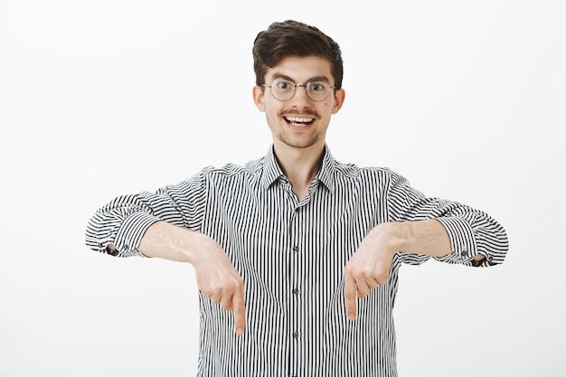 Excited and fascinated attractive caucasian male model with moustache in trendy round glasses, smiling joyfully while pointing down with index fingers, being wondered and thrilled with something cute