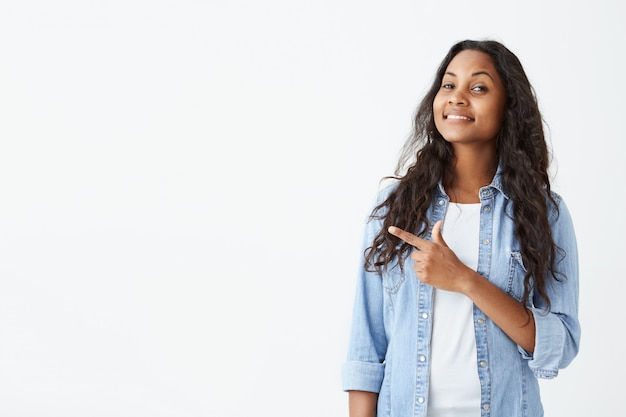 Excited and fascinated young dark-skinned female student in light-blue shirt and long wavy hair indicating something great on white wall with copy space for your text or promotional content.