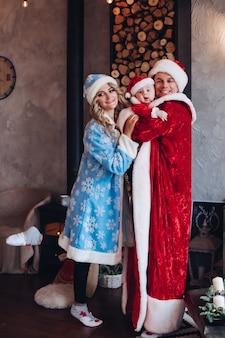 新年のコンセプト写真のポーズをとっている間、彼の赤ちゃんと妻を抱き締めるサンタの服を着て興奮した父親