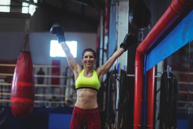 Возбужденная женщина-боксер позирует после победы