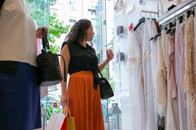 패션 매장에서 선반에 드레스를 쳐다보고 흥분된 여성 고객. 낮은 각도, 솔직한 샷. 부티크 또는 소매 개념