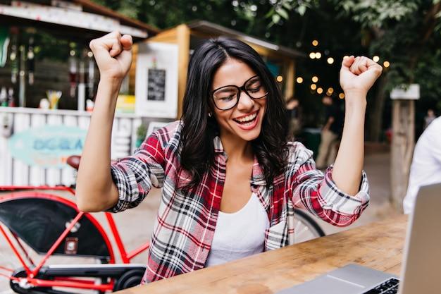 屋外カフェで働く興奮した女性フリーランサー。ノートパソコンで通りに座っている感情的なブルネットの少女の肖像画。